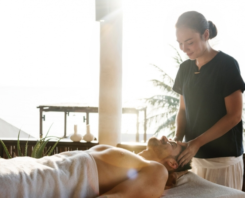 Woman offering massage therapy to a happy client