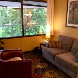 A cozy room with a chair and couch where counseling take place.